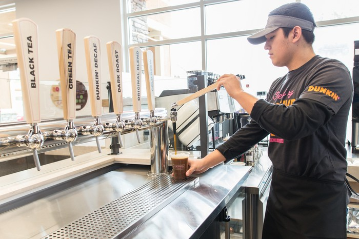 A Dunkin' employee fills a coffee cup.