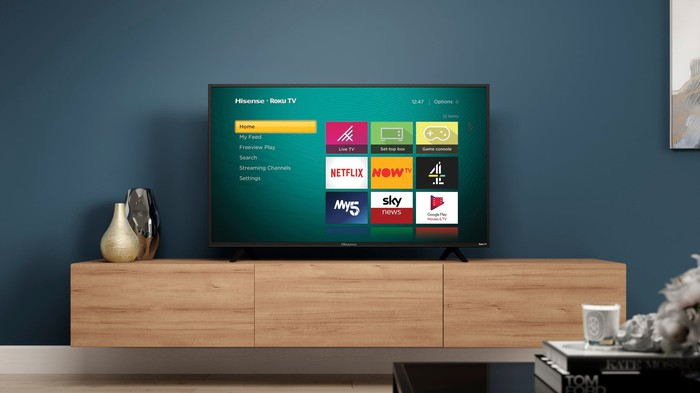 A Hisense TV featuring the Roku operating system showing streaming channel options.