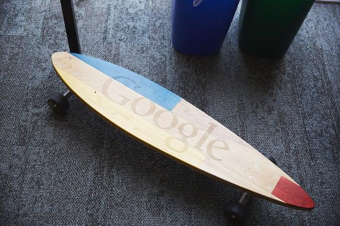 A Google skateboard on a dark office floor.
