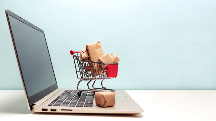 A tiny shopping cart, laden with packages wrapped in brown paper, stands on the keyboard of a laptop computer.