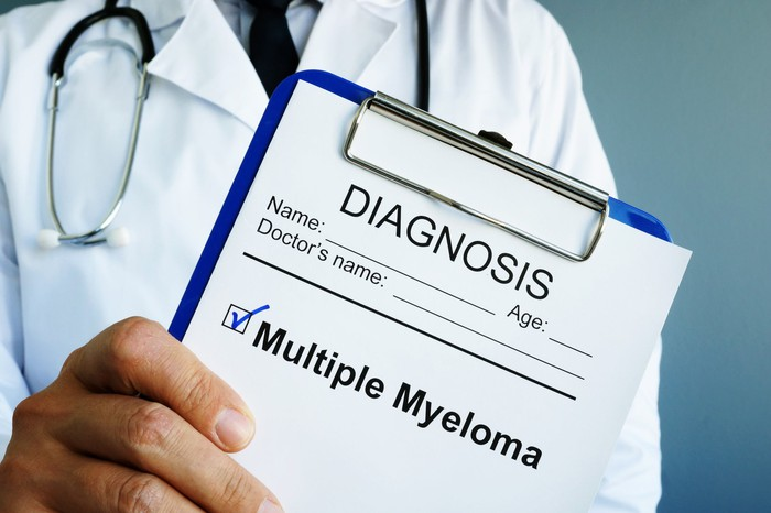 A person in a lab coat with a stethoscope holding a clipboard that has a check mark next to the words multiple myeloma.