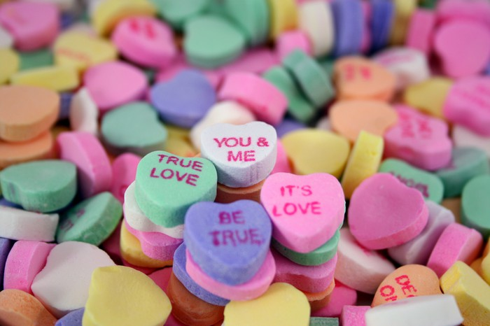 An assortment of Valentine's Day candy hearts with love-themed phrases printed on them.