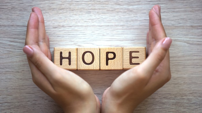 """Woman's hands holding letter cubes spelling out the word """"hope."""""""