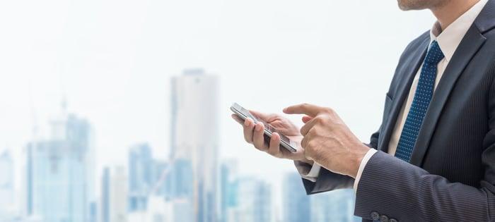 A businessman uses a smartphone.