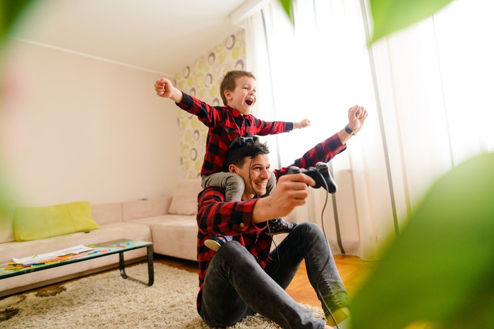 A child on his dad's shoulders cheers his dad, who is playing a console video game in the living room