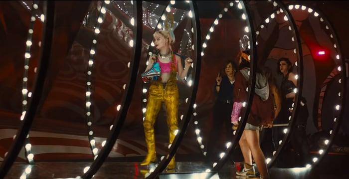 The Birds of Prey team walk down a brightly lit tunnel, led by Margot Robbie as Harley Quinn, in a stillframe from Harley Quinn: Birds of Prey.