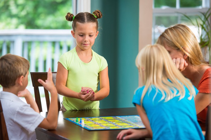 Four children playing a board game at a table