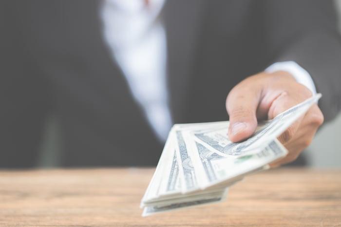 Businessman in suit handing over money