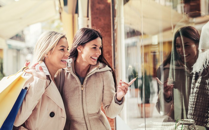 Photograph of two women looking into store window.