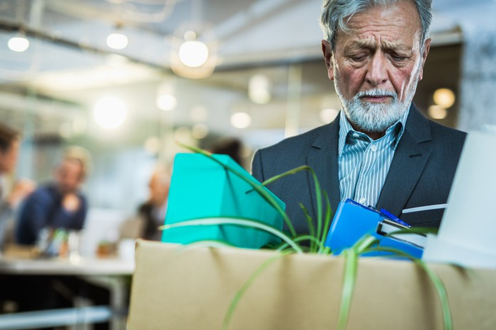 An older person in a suit packing his belongings in a cardboard box.