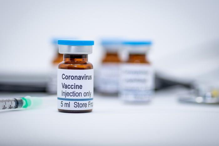 Multiple coronavirus vaccine dose bottles on a surface.