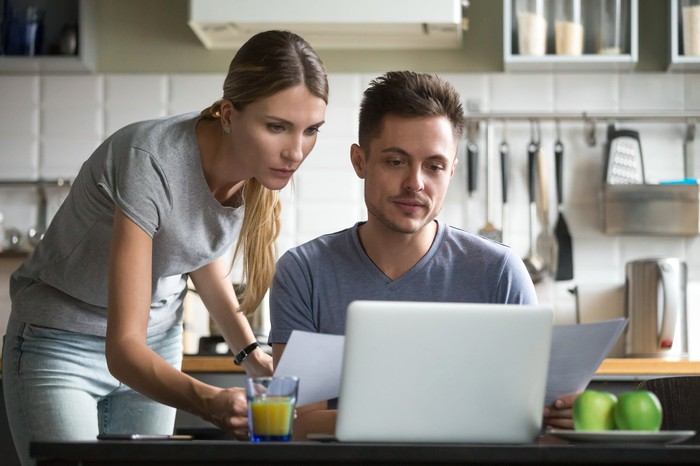 Man sitting at laptop while woman stands next to him