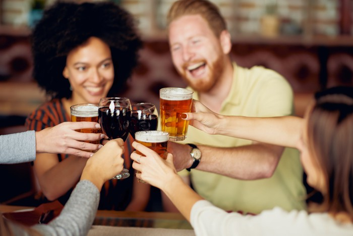 Friends drink beer at a bar.