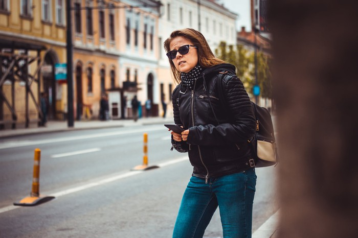 Young woman in sunglasses and black leather jacket holding phone in a city as she looks for her ride.