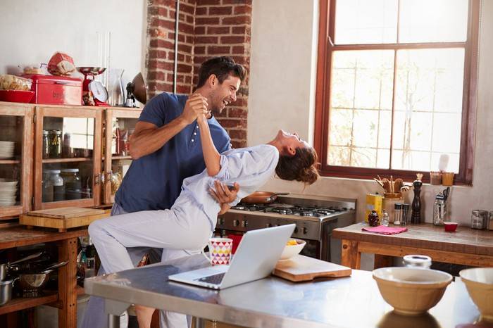 A man and a woman dance in a kitchen.