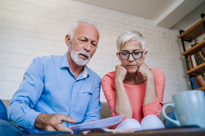An older couple looking at papers together on the couch
