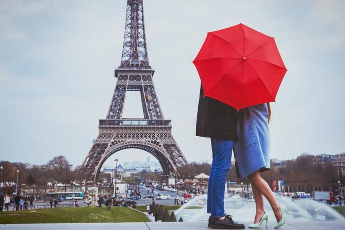 A couple kiss behind an umbrella at the Eiffel Tower