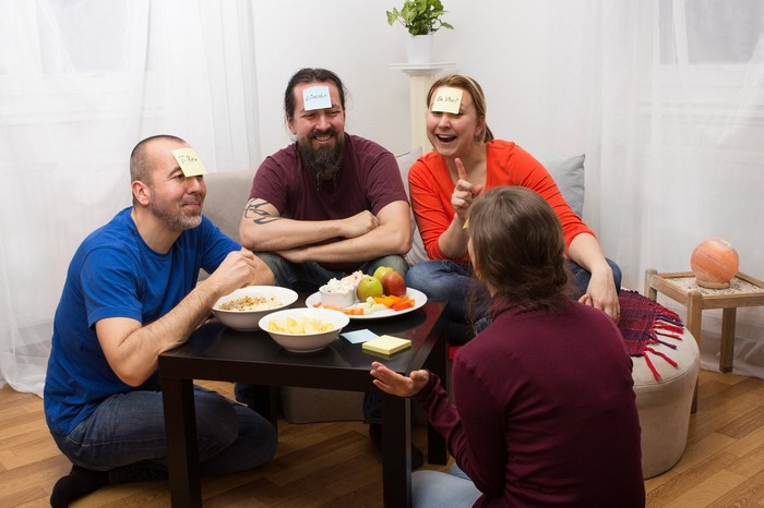 Four friends are around a table, with cards on their foreheads, playing a game and laughing.