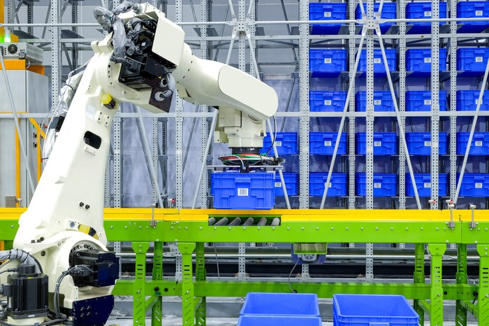 Warehouse robot moving a bin on a conveyor belt.