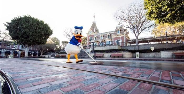 A costumed Donald Duck sweeping Main Street U.S.A. in Disneyland.