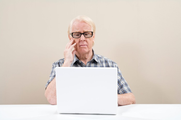 Older man with sad expression sitting at laptop