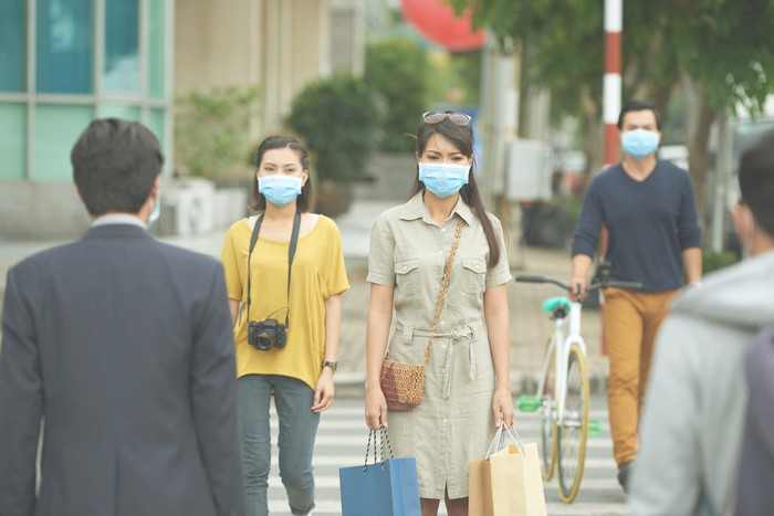 People with face masks walking on the sidewalk