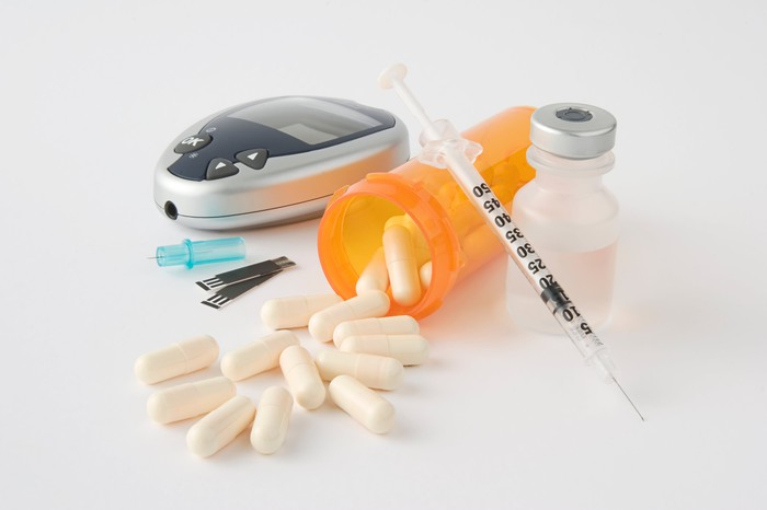 Pills alongside an insulin vial, a syringe, and a glucose meter.