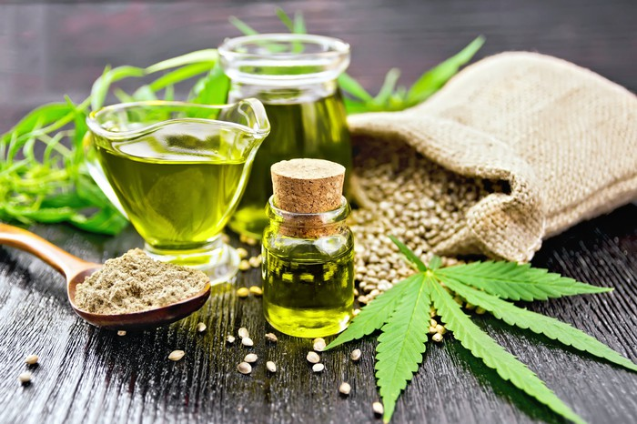 A glass jar of cannabis hemp oil on the table with hemp seeds and a marijuana leaf