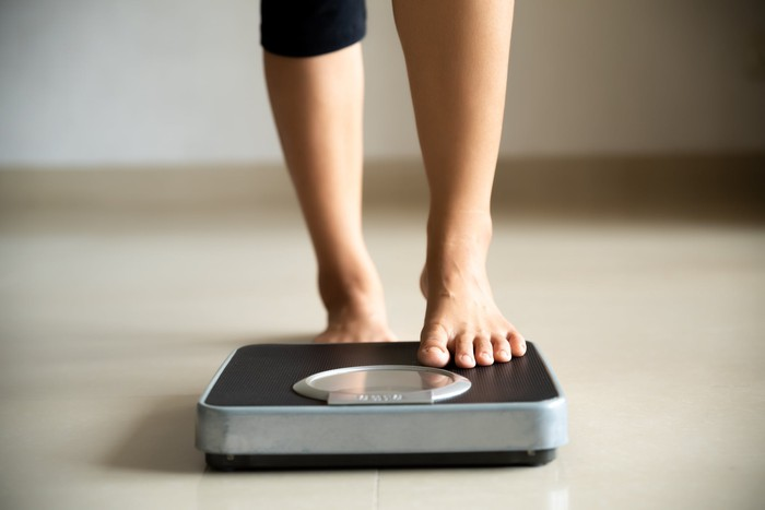 Legs stepping onto a scale