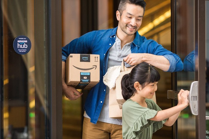 A man and child walking out of an Amazon Hub, with the man holding an Amazon package under his right arm.
