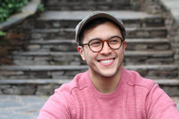 Smiling young man in glasses and hat
