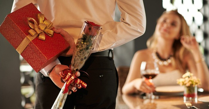 A guy holding a rose and gift box behind his back as he approaches his date at a table cradling a glass of wine.