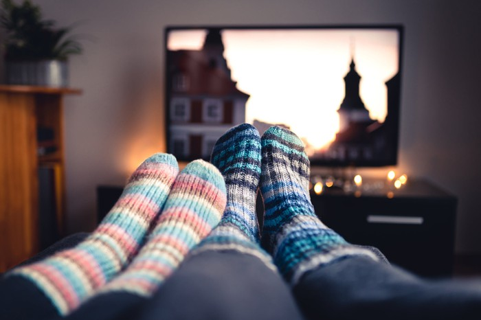 Two pairs of feet with colorful socks snuggled together, with a large TV in the background.
