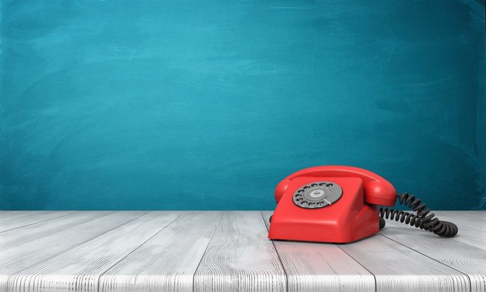 Red rotary dial telephone on a grey table