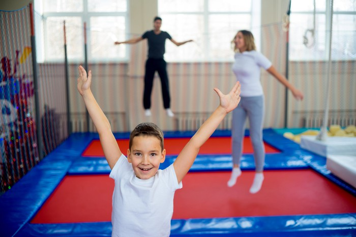 Kid in foreground jumping on a trampoline