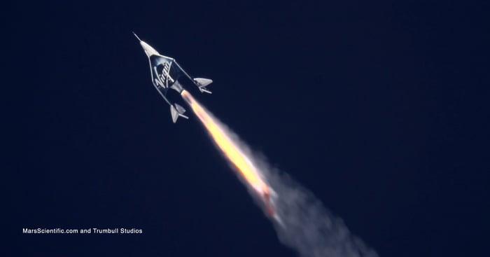 A spacecraft takes flight against a dark background.