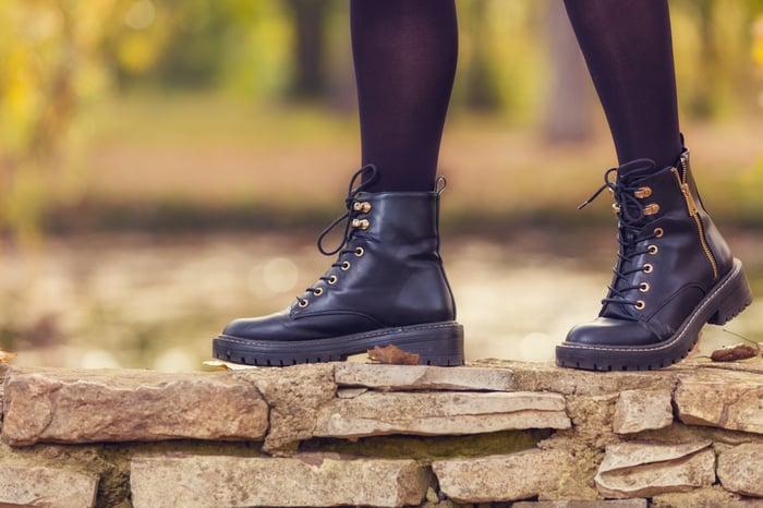 A girl walks on a stone wall wearing stylish rugged boots.