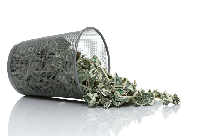 An overturned wastepaper basket spills crumpled dollar bills