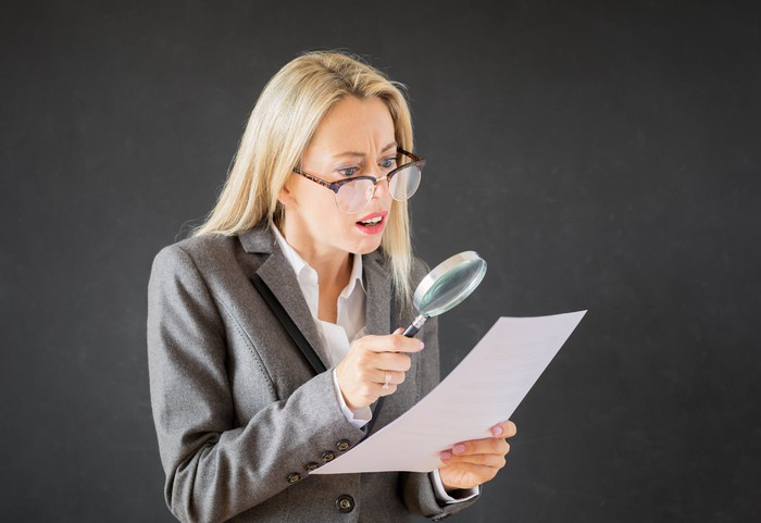 A woman looking at a piece of paper through a magnifying glass.