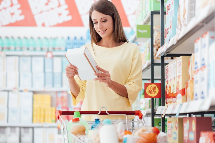 A woman stands with a cart in a discount store and looks at a box of cereal.