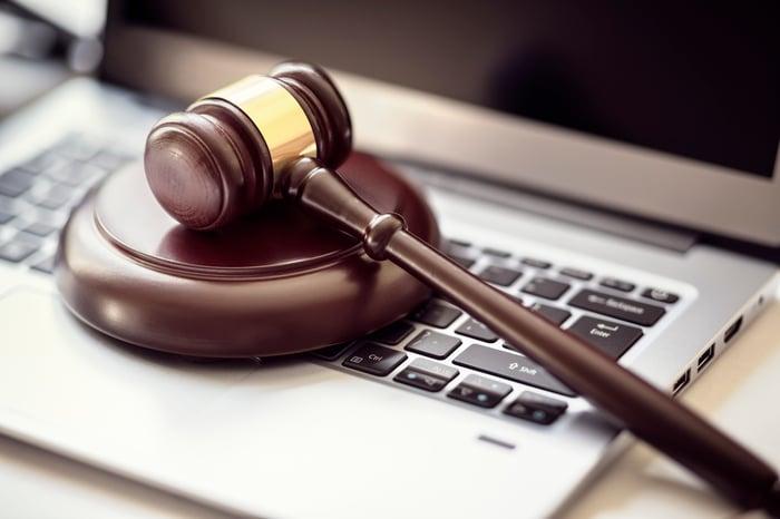 A gavel sits atop a laptop computer.