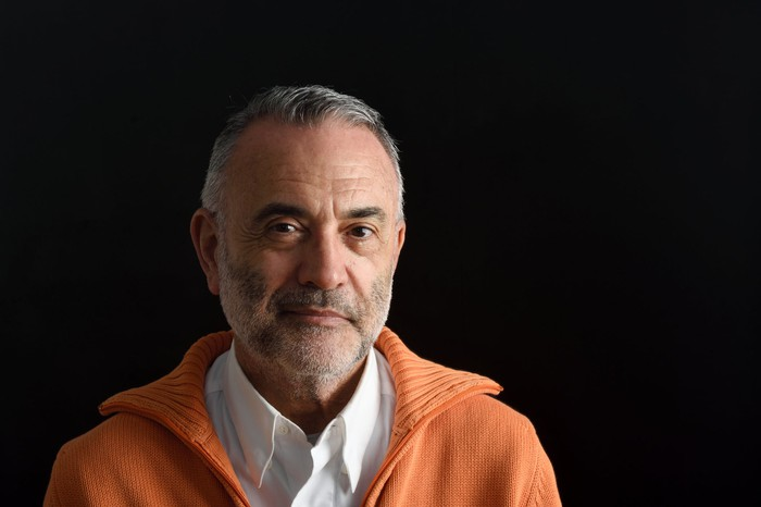Serious older man wearing an orange sweater while standing against black background