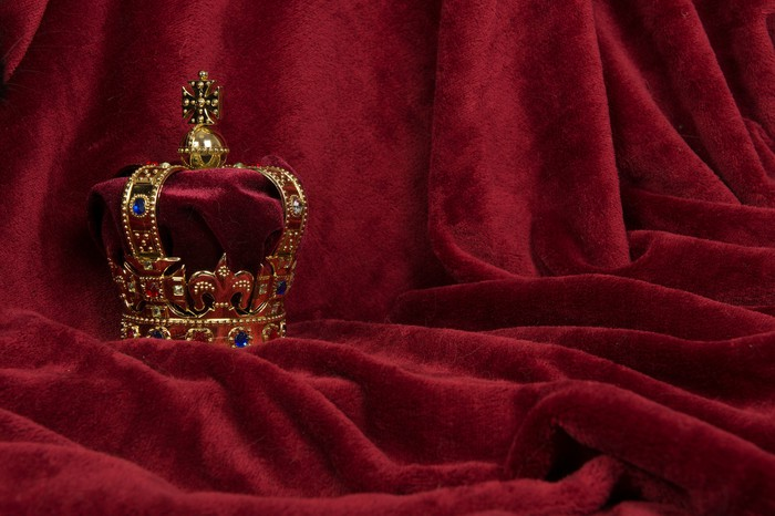 An ornate crown displayed against a purple fabric.
