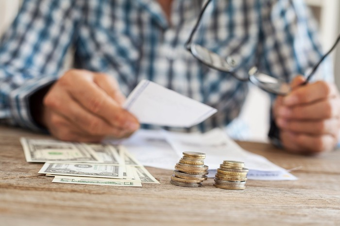 A man removing his glasses and looking at paperwork on the table near some cash and coins