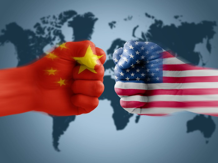 Two fists meet, one emblazoned with Chinese flag and one with U.S. flag