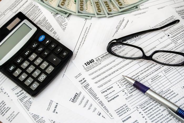 Tax returns, calculator, glasses, pen, and money.
