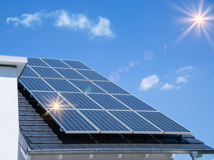 Set of 20 solar panels on a roof, with the sun shining above it.