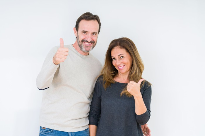 A middle-aged couple smiling and each giving the thumbs up sign.