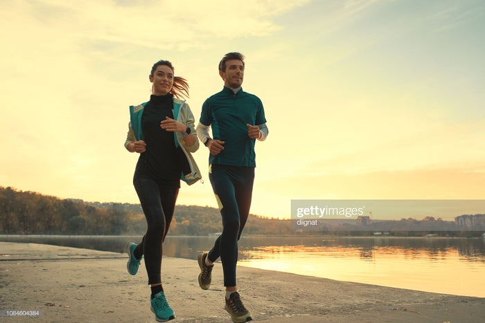 Young woman and young man running along a lake at sunrise of sunset.
