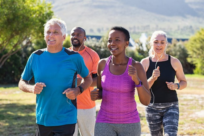 For middle-aged people -- a white woman, a black woman, a white man, and a black man -- running in a park during warm weather.